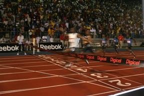 Usain Bolt crosses the finish line;