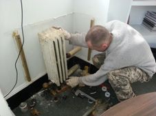 Maintenance worker Andrey Chekalov replaces a steam trap and corrects the pitch of a radiator in the Arsenal;