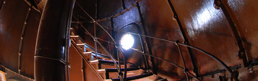 Sunlight streams through a door inside a large winding staircase.
