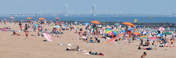 Sunbathers and swimmers fill the beach at Coney Island