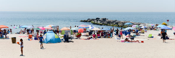 Sunbathers and swimmers fill the beach at Rockaway Beach