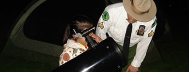 A park ranger assists a child looking through a large telescope