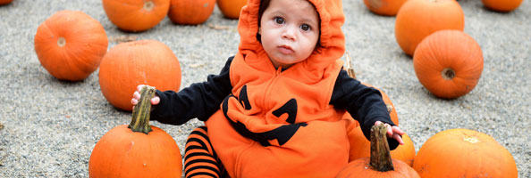 Baby in a jack-o-lantern costume sitting among pumpkins