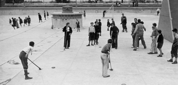 Image of Highbridge Park Pool being used for shuffleboard, volleyball, and other sports in the off-season. October 1, 1936. Neg. 9721.