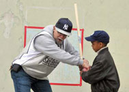 Man helping child playing stick ball at Street Games