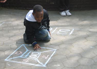 Child playing a chalk game at Street Games
