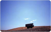 Payahuler climbs a mountain on its way to dump garbage at Fresh Kills, 1999, photo by Michael Falco