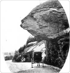 A rock projects over a carriage path in Central Park, circa 1870-1871.