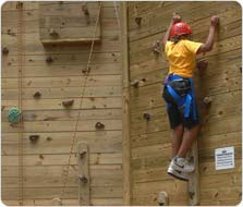 Climbing a wall at the adventure course