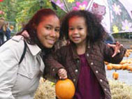 Woman and girl posing with a pumpkin