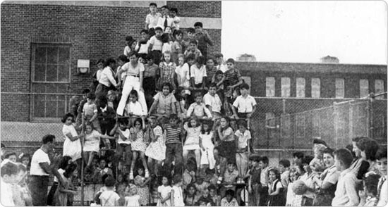 Masses of children climb the jungle gym adjacent to PS 21 in the Bronx, September 27, 1943. Courtesy of Parks Photo Archive; Neg. 22675.