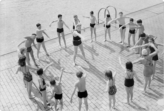 Children gathers around a Learn to Swim program instructor and practice their strokes, 1940. Courtesy of Parks Photo Archive, Neg. 53237-1.