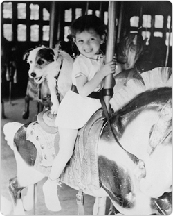 A young girl and her dog share a carousel ride.