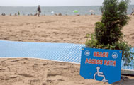 Sign next to beach mat saying Beach Access Path