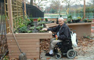 Park visitor in wheelchair interacts with sensory garden