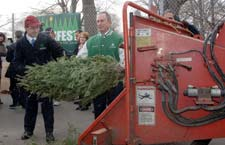 Mayor Bloomberg and Comissioner Benepe feeing a tree into a chipper