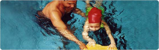 Man teaching child to swim with kickboard