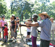 Urban Park Ranger instructs parkgoer in the art of archery.