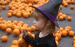 Girl in witch costume with pumpkins in background