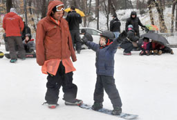 an excited child learning to snowboard