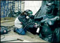 Photo of conservator working on a sculpture