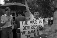 Vietnam War protester carrying sign: