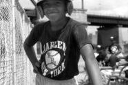 Boy with baseball helmet and bat, Harlem RBI's