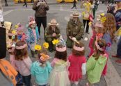 Children, adorned in flowers, gather around Urban Park Rangers