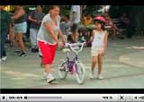 Video still of adult teaching child to ride bike