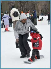 Child learning how to snowboard