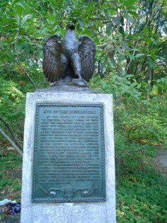 Eagle on integral plinth on stele on base, two plaques (one mounted on stele, one in ground before stele)