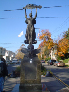 Female figure atop ball on integral plinth fronted by eagle rampant and backed by wreathed helmet, pedestal, base, four plaques