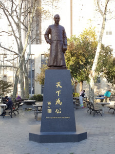 . Bronze figure (heroic size) of Dr. Sun Yat-sen;  proper left hand holding a hat. Granite pedestal, with inscription at middle of east and west  side.