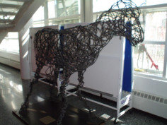 Sculpture of horse made out of a continuous piece of steel, on flat metal base