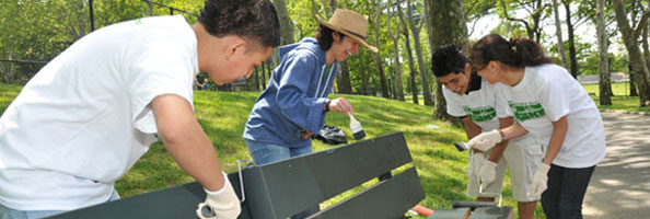 Volunteers painting a park bench