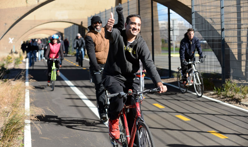 A man showing a thumbs up leads a group on a bike ride on a greenway.
