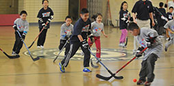 kids playing street hockey in a gym