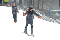 a woman helps another woman to learn how to ski on a snow-covered slope