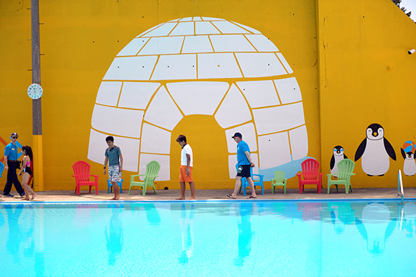 Kids and their families walk by a wall decal of an igloo and penguins at Fisher Pool.