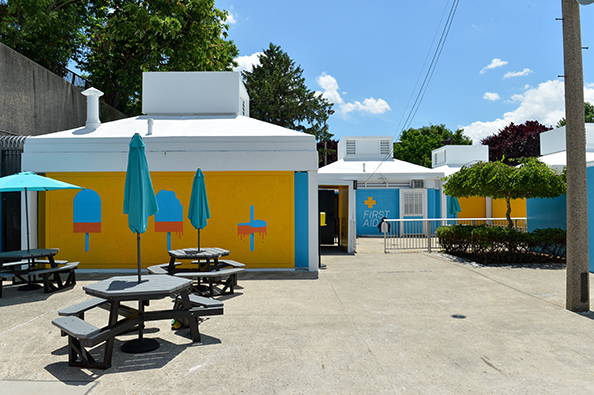 Fisher pool's picnic area is enhanced by blue umbrellas and vibrant decals and paint on the walls.