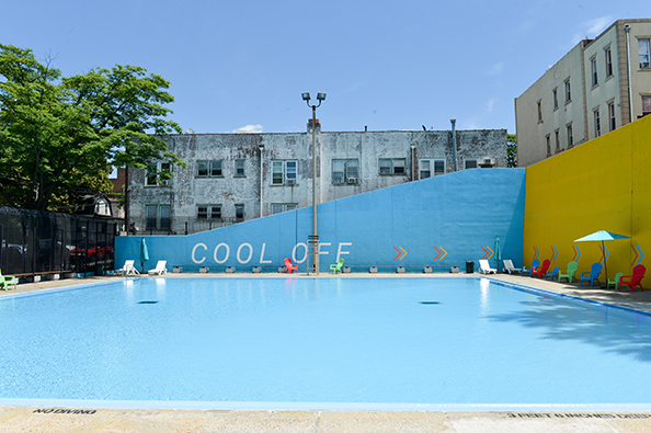 "Fisher Pool's back wall reads ""cool off"" with arrows leading to the other wall decals. Around the pool are brightly-colored lounge chairs."