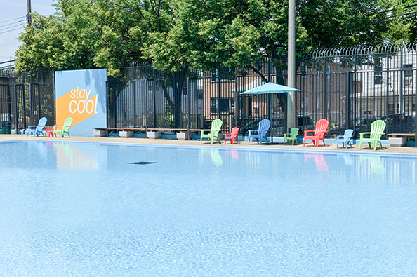 "Across Fisher Pool is a yellow and blue wall with ""stay cool"" decals, and chairs and umbrellas at the pool side."