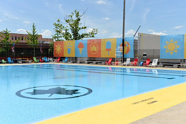 On Douglas and DeGraw's pool wall is a banner decorated with summer-themed art: a sun, water bottle, ice cream cone, park leaf, popsicle, and beach ball.