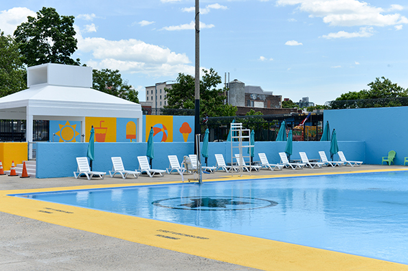 At Douglas and DeGraw pool there are lounge chairs with umbrellas placed along the pool side.