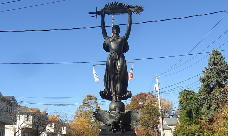 A female figure in bronze stands on a granite pedestal holding a sword and palm frond high in the air while an eagle with its wings spread sits at her feet.