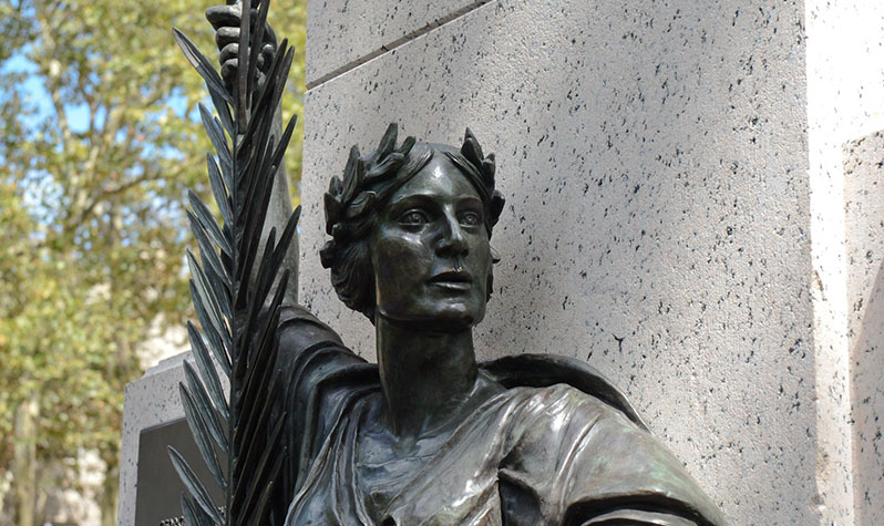 Cropped photo showing the head and bust of a bronze statue of a female figure wearing a laurel wreath crown and holding a palm frond.