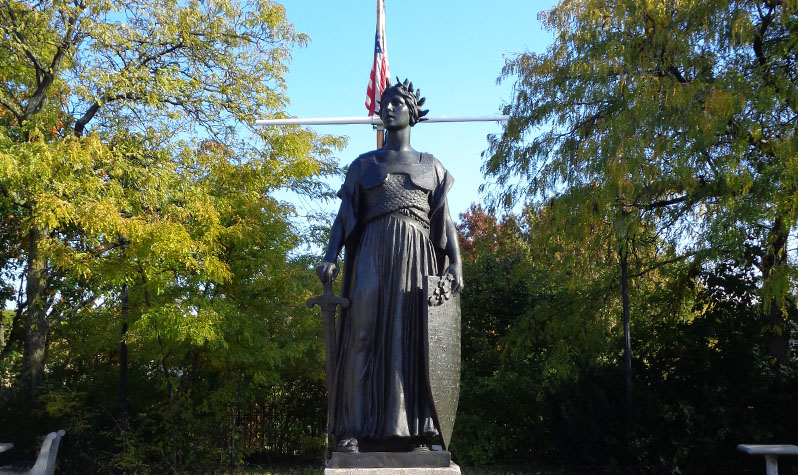 A seven-foot-tall female figure bears a sword in her right hand and an inscribed shield in her left.