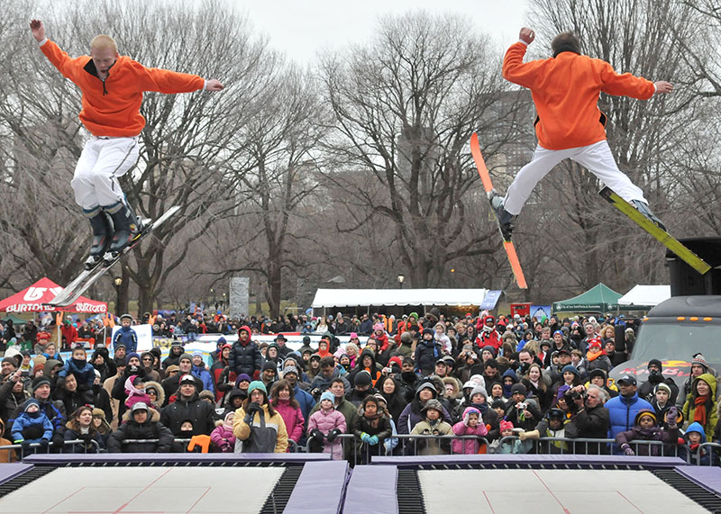 Two performers show the audience trampoline ski.