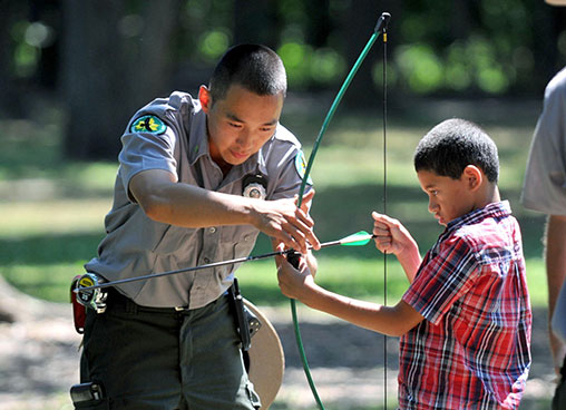 A ranger shows a kid how to use a bow and arrow