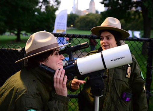 A park ranger looks through a telescope to look to the stars